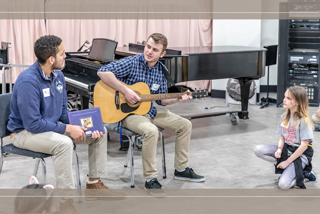 Two Neag School students with young local student in music room.