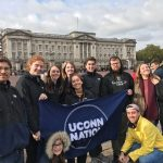 Neag School students in London holding a UConn Nation banner.